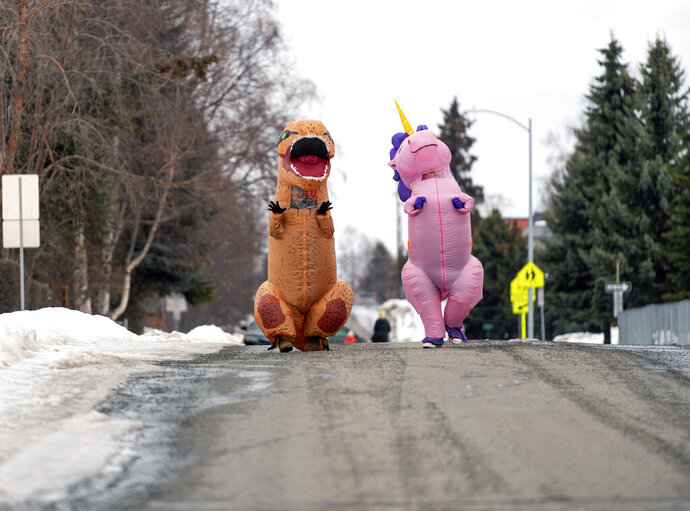 Christine Hohf, wearing a unicorn costume, right,and Andi Correa, wearing a dinosaur costume, walk through South Addition, Wednesday, March 25, 2020 in Anchorage. Hohf, who works as a scrub tech at a surgery center, said her hours were cut due to elective surgeries being put off because of the coronavirus pandemic, and she wanted to do something that would make people smile. (Loren Holmes/Anchorage Daily News via AP)
