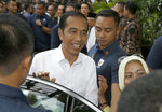 Incumbent Indonesian President Joko Widodo, center, pauses to be taken a photo by supporters as he leaves after a meeting with leaders of his coalition parties in Jakarta, Indonesia, Thursday, April 18, 2019. Widodo said Thursday he was won re-election after receiving an estimated 54% of the vote, backtracking on an earlier vow to wait for official results after his challenger made improbable claims of victory. (AP Photo/Achmad Ibrahim)