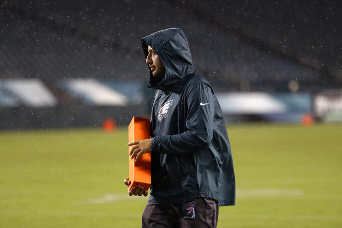 A worker removes sideline markers after a storm ended a preseason NFL football game between the Philadelphia Eagles and the Baltimore Ravens, Thursday, Aug. 22, 2019, in Philadelphia. (AP Photo/Michael Perez)