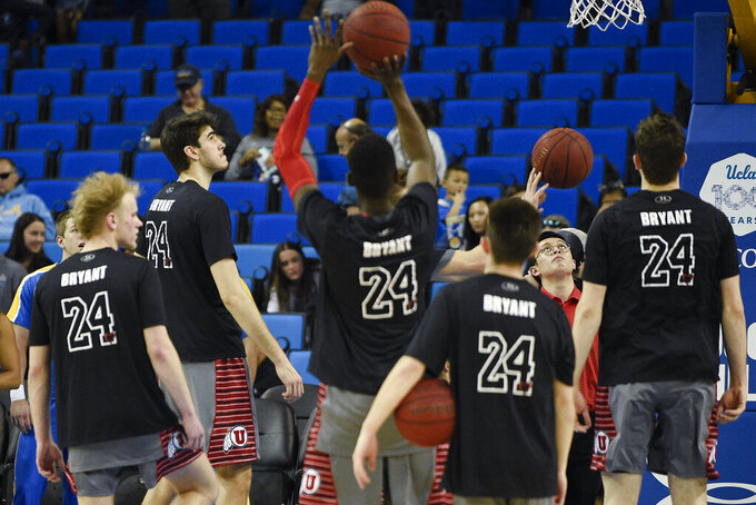 Utah players wear shirts with No. 24 on the back in honor of late Los Angeles Lakers player Kobe Bryant while warming up prior to an NCAA college basketball game against UCLA in Los Angeles, Sunday, Feb. 2, 2020. (AP Photo/Kelvin Kuo)