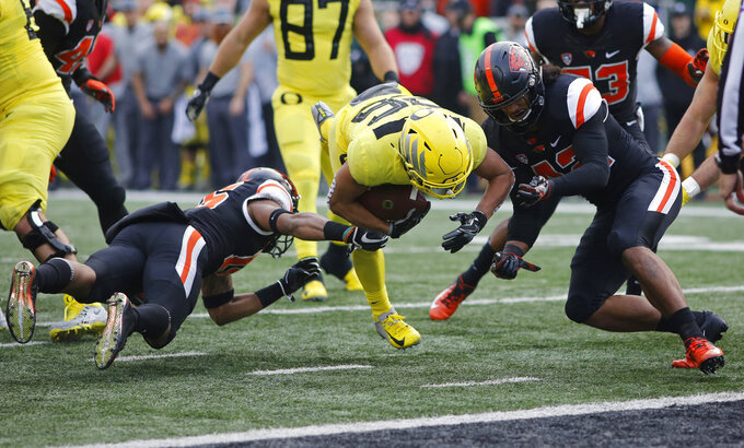 Oregon running back Travis Dye, center, tries to get past Oregon State's Jeffrey Manning Jr., left, and Doug Taumoelau, right, in the first half of an NCAA football game in Corvallis, Ore., on Friday, Nov. 23, 2018. (AP Photo/Timothy J. Gonzalez)