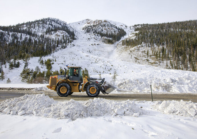 FILE - In this March 5, 2019 file photo, crews work to remove the snow debris from a controlled avalanche that spilled onto Interstate 70 near Loveland Pass, Colo. Historic avalanche conditions persisted in the mountains of Colorado on Thursday, March 7, 2019, shutting down portions of I-70 and prompting a rare warning for drivers to avoid traveling through the region that's home to many ski resorts.  (Hugh Carey/Summit Daily News via AP, File)