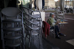 A customer sitss at a restaurant as it closes in Marseille, southern France, Sunday Sept. 27, 2020. As restaurants and bars in Marseille prepared Sunday to shut down for a week as part of scattered new French virus restrictions, Health Minister Olivier Veran insisted that the country plans no fresh lockdowns. (AP Photo/Daniel Cole)