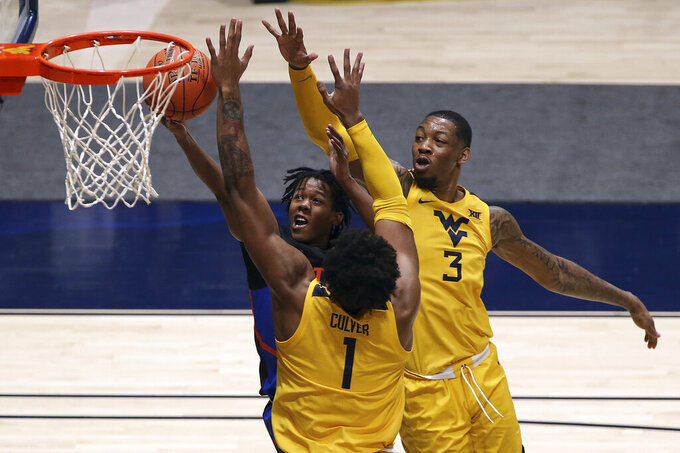Florida guard Tyree Appleby (22) shoots while defended by West Virginia forwards Derek Culver (1) and Gabe Osabuohien (3) during the second half of an NCAA college basketball game Saturday, Jan. 30, 2021, in Morgantown, W.Va. (AP Photo/Kathleen Batten)