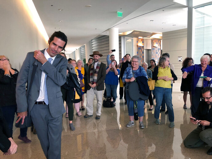 Scott Warren, left, of Ajo, Ariz., thanks his supporters and attorneys after walking out of court in Tucson, Ariz. on Wednesday, Nov. 20, 2019, after being acquitted of two counts of harboring in a case that garnered international attention. Prosecutors said Warren illegally helped two migrants avoid authorities. He said he was fulfilling his humanitarian duties by helping two injured men. (AP Photo/Astrid Galvan)