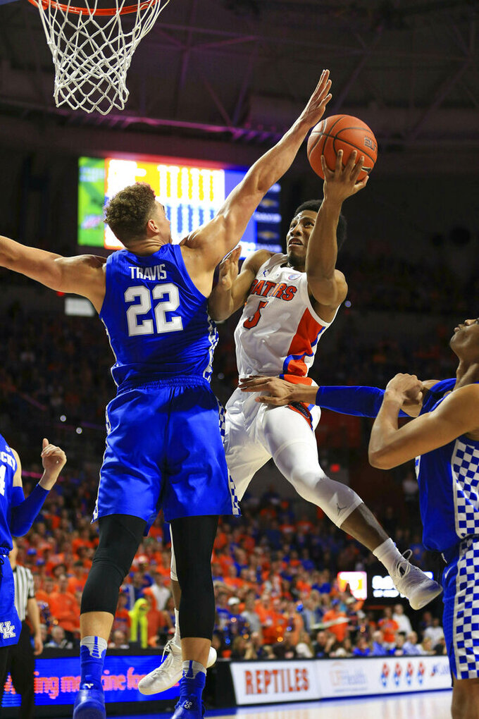 FILE - In this Saturday, Feb. 2, 2019, file photo, Florida guard KeVaughn Allen scores over Kentucky forward Reid Travis during the first half of an NCAA college basketball game in Gainesville, Fla. Florida is trying to get back to the NCAA Tournament for the third consecutive year. (AP Photo/Matt Stamey, File)