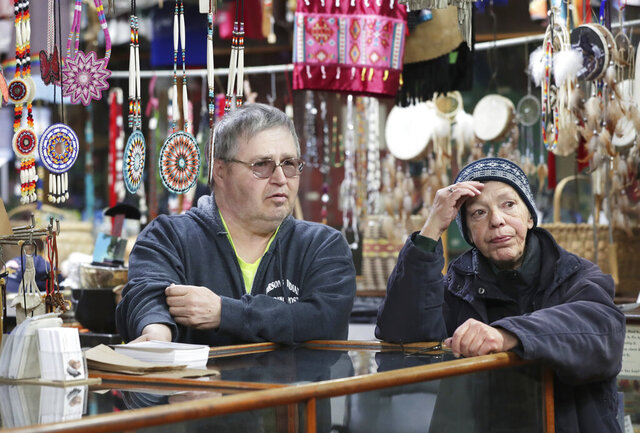 In this Thursday, March 26, 2020 photo, Henry and Candice Lukasavage, who have owned Parson's Indian Trading Post & Museum since 1994, stand in the museum space at their business in Lake Delton, Wis. It's one of the oldest tourist businesses in the state and has been at its current location since 1919. (Amber Arnold/Wisconsin State Journal via AP)
