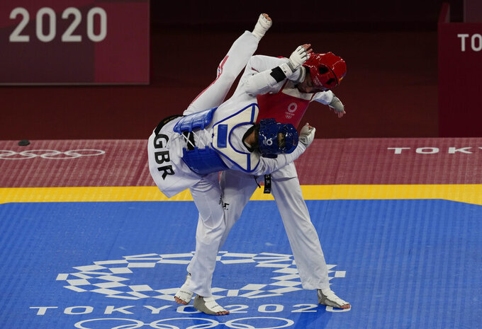 Kimia Alizadeh Zonoozi, Refugee Olympic Team, right, is attacked by Britain's Jade Jones during the taekwondo women's 57kg match at the 2020 Summer Olympics, Sunday, July 25, 2021, in Tokyo, Japan. (AP Photo/Themba Hadebe)