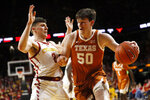 Texas center Will Baker drives past Iowa State guard Caleb Grill, left, during the second half of an NCAA college basketball game, Saturday, Feb. 15, 2020, in Ames, Iowa. (AP Photo/Charlie Neibergall)