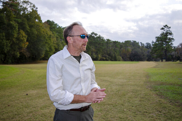 Jeffrey Shanks, an archaeologist with the National Park Service, visits an unmarked slave cemetery on Dec. 16, 2019, at the Capital City Country Club in Tallahassee, Fla.  Shanks earlier this year brought in ground-penetrating radar and two cadaver-sniffing dogs to investigate if long-told stories about a cemetery at the golf course are true. His search indicates that there are at least 40 graves near the 7th hole tee. (AP Photo/Bobby Caina Calvan)