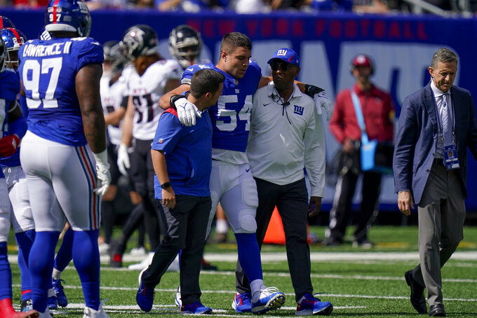 New York Giants inside linebacker Blake Martinez (54) is walked off the field after an apparent injury during the first half of an NFL football game against the Atlanta Falcons, Sunday, Sept. 26, 2021, in East Rutherford, N.J. (AP Photo/Seth Wenig)