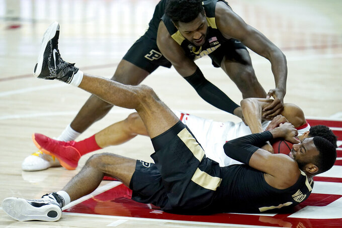 Maryland guard Aaron Wiggins, center, competes for a loose ball with Purdue forward Trevion Williams, top, and forward Aaron Wheeler during the first half of an NCAA college basketball game, Tuesday, Feb. 2, 2021, in College Park. (AP Photo/Julio Cortez)
