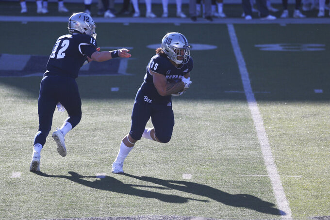 Nevada quarterback Carson Strong hands off to running back Toa Taua in the first half of an NCAA football game against San Diego State, Saturday, Nov. 21, 2020, in Reno, Nev. (AP Photo/Lance Iversen)
