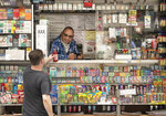 A man buys a cold drink at a news stand, Thursday, July 30, 2020, in New York. Stocks are falling on Wall Street Thursday after reports showed that layoffs are continuing at a stubborn pace and that the U.S. economy contracted at a nearly 33% annual rate in the spring. (AP Photo/Mark Lennihan)