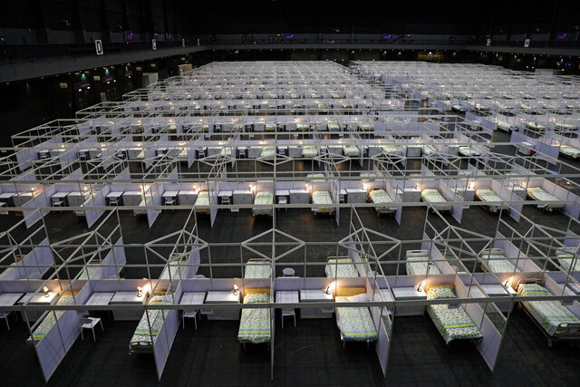Rows of beds are seen at a temporary field hospital set up at Asia World Expo in Hong Kong, Saturday, Aug. 1, 2020. The new COVID-19 patient holding facility can accommodate up to 500 adult patients in stable conditions. The facility which is located near the Hong Kong International Airport is a big convention and exhibition facility and was previously used as a coronavirus testing center for incoming travelers. It's transformed into a treatment facility so that it helps freeing up hospital beds for the serious patients. (AP Photo/Kin Cheung)