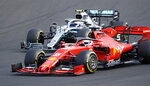 Ferrari driver Sebastian Vettel, bottom, of Germany, leads Mercedes driver Valtteri Bottas, foreground, of Finland, during the Hungarian Formula One Grand Prix at the Hungaroring racetrack in Mogyorod, northeast of Budapest, Hungary, Sunday, Aug. 4, 2019. (AP Photo/Laszlo Balogh)
