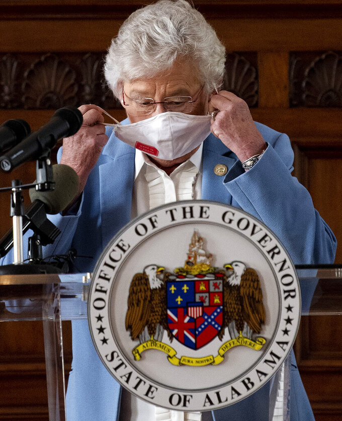 Governor Kay Ivey removes her mask as she asks citizens to continue wearing masks and use social distancing during a coronavirus update in the state capitol building in Montgomery, Ala., on Tuesday June 29, 2020. (Mickey Welsh/The Montgomery Advertiser via AP)