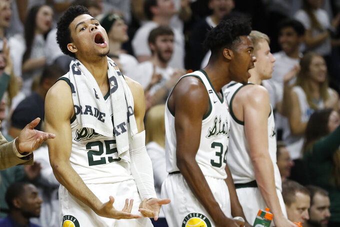 Michigan State forward Malik Hall (25) and forward Julius Marble (34) react after a 3-point basket by a teammate during the second half of an NCAA college basketball game against Northwestern, Wednesday, Jan. 29, 2020, in East Lansing, Mich. (AP Photo/Carlos Osorio)