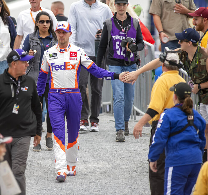 Denny Hamlin (11) greets a fan on his way to driver introductions at the Drydene 400 - Monster Energy NASCAR Cup Series playoff auto race, Sunday, Oct. 6, 2019, at Dover International Speedway in Dover, Del. (AP Photo/Jason Minto)