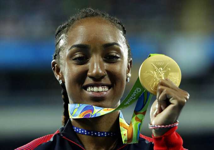 FILE - In this Thursday, Aug. 18, 2016 file photo, Gold medal winner Brianna Rollins from the United States shows off her medal during the medal ceremony for the women's 100-meter hurdles final during the athletics competitions of the 2016 Summer Olympics at the Olympic stadium in Rio de Janeiro, Brazil. Rollins-McNeal has been provisionally suspended for a suspected doping rules violation it was reported on Thursday, Jan. 14, 2021. Rollins-McNeal won Olympic gold in the women's 100-meter hurdles for the United States at the 2016 Rio de Janeiro Games.  (AP Photo/Dmitri Lovetsky, File)