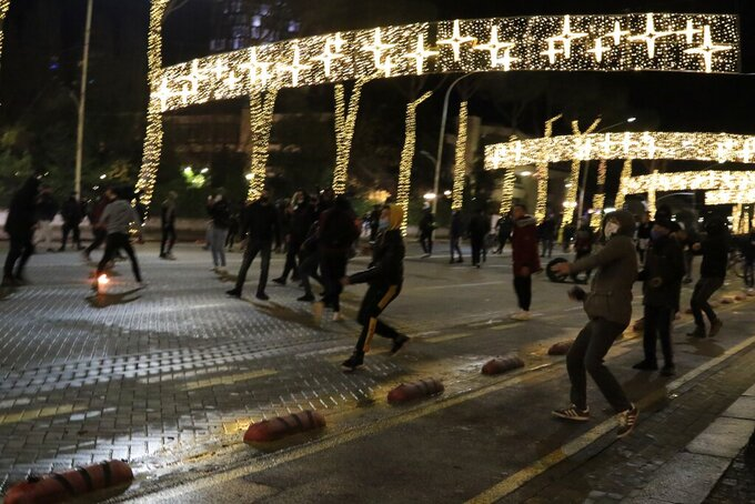 Protesters throw stones to riot police during clashes in Tirana, Friday, Dec. 11, 2020. Albanian demonstrators clashed in the third day on Friday protesting for the death of a 25-year-old man shot dead by a police officer. (AP Photo/Hektor Pustina)