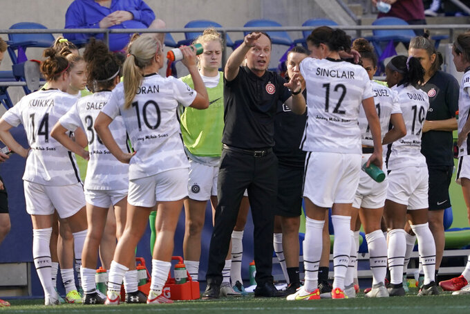 Portland Thorns FC head coach Mark Parsons, center, talks to his team during the first half of an NWSL soccer match against OL Reign, Sunday, Aug. 29, 2021, in Seattle. (AP Photo/Ted S. Warren)