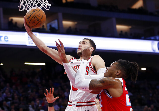 Chicago Bulls guard Zach LaVine, left, goes to the basket against Sacramento Kings forward Richaun Holmes, right, during the first quarter of an NBA basketball game Monday, Dec. 2, 2019, in Sacramento, Calif. (AP Photo/Rich Pedroncelli)