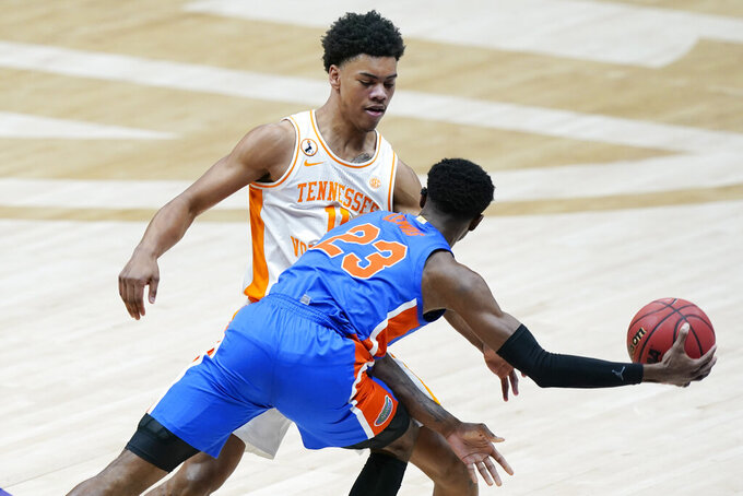Florida's Scottie Lewis (23) passes the ball around Tennessee's Jaden Springer (11) in the first half of an NCAA college basketball game in the Southeastern Conference Tournament Friday, March 12, 2021, in Nashville, Tenn. (AP Photo/Mark Humphrey)