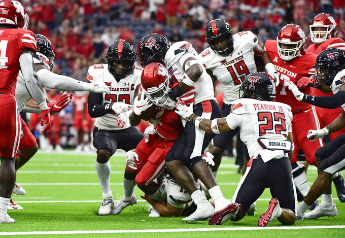 Houston running back Ta'Zhawn Henry (4) is tackled short of the goal line by Texas Tech during the first half of an NCAA college football game Saturday, Sept. 4, 2021, in Houston. (AP Photo/Justin Rex)