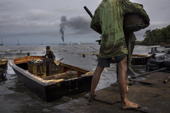 Fishermen covered in oil get their boat ready for fishing on Lake Maracaibo near La Salina crude oil shipping terminal in Cabimas, Venezuela, July 9, 2019. Nobody lives as closely with the environmental fallout of Venezuela's collapsing oil industry as the fishermen who scratch out an existence on the blackened, sticky shores of Lake Maracaibo. (AP Photo/Rodrigo Abd)