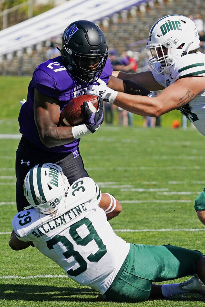 Northwestern running back Anthony Tyus III (27) is tackled by Ohio safety Michael Ballentine (39) and defensive end Bryce Stai during the first half of an NCAA college football game in Evanston, Ill., Saturday, Sept. 25, 2021. (AP Photo/Nam Y. Huh)