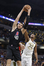 Los Angeles Clippers' Ivica Zubac (40) grabs a rebound against Indiana Pacers' Myles Turner (33) during the first half of an NBA basketball game, Monday, Dec. 9, 2019, in Indianapolis. (AP Photo/Darron Cummings)