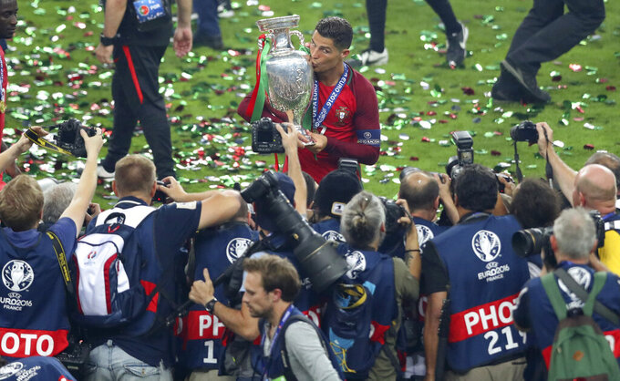 FILE - In this Sunday, July 10, 2016 file photo, Portugal's Cristiano Ronaldo celebrates with the trophy after winning the Euro 2016 final soccer match between Portugal and France at the Stade de France in Saint-Denis, north of Paris. When it comes time for Brazilians to choose who to watch on the soccer field this month — Neymar or Kylian Mbappé, Lionel Messi or Cristiano Ronaldo — the response might be surprising. Because of an unusual set of circumstances, it will be the European Championship that reaches more viewers in Brazil than the Copa America — even though Brazil is expected to host South American the tournament under a completely different set of unusual circumstances. (AP Photo/Thibault Camus, File)