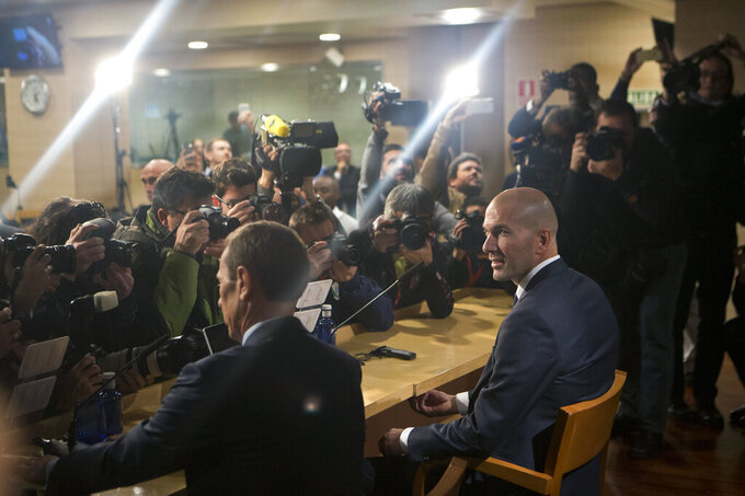 FILE - In this file photo dated Jan. 5, 2016, Real Madrid's coach Zinedine Zidane, right, sits down in front of the media prior a press conference at the Santiago Bernabeu stadium in Madrid, Spain. Zinedine Zidane is again stepping down as Real Madrid coach. The club says the Frenchman is leaving his job. It comes four days after a season in which Madrid failed to win a title for the first time in more than a decade. (AP Photo/Paul White, File)