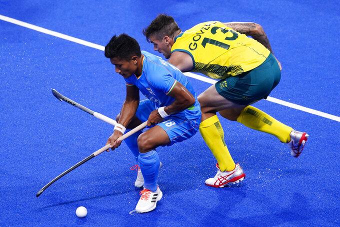 Australia's Blake Govers (13) and India's Nilakanta Sharma (18) battle for the ball during a men's field hockey match at the 2020 Summer Olympics, Sunday, July 25, 2021, in Tokyo, Japan. (AP Photo/John Minchillo)