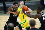 Colorado guard McKinley Wright IV, right, steals the ball from Oregon guard Chris Duarte, center, who drives the lane past Colorado guard Eli Parquet in the second half of an NCAA college basketball game Thursday, Jan. 7, 2021, in Boulder, Colo. (AP Photo/David Zalubowski)