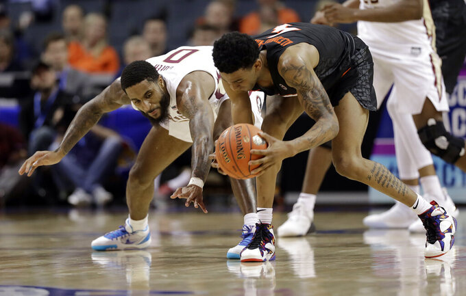 Florida State's Phil Cofer (0) and Virginia Tech's Nickeil Alexander-Walker (4) chase a loose ball during the second half of an NCAA college basketball game in the Atlantic Coast Conference tournament in Charlotte, N.C., Thursday, March 14, 2019. (AP Photo/Chuck Burton)