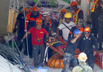 Rescuers carry an earthquake survivor after being pulled out from the rubble of a commercial building following a 6.1 magnitude earthquake in Porac township, Pampanga province, north of Manila, Philippines, Tuesday, April 23, 2019. The strong earthquake struck the northern Philippines Monday trapping some people in a collapsed building, damaged an airport terminal and knocked out power in at least one province, officials said. (AP Photo/Bullit Marquez)