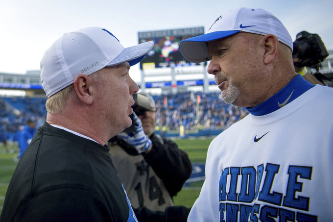 Kentucky head coach Mark Stoops speaks with Middle Tennessee head coach Rick Stockstill after an NCAA college football game against Kentucky in Lexington, Ky., Saturday, Nov. 17, 2018. Kentucky defeated Middle Tennessee 34-23. (AP Photo/Bryan Woolston)