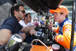 FILE - NASCAR driver Jimmie Johnson, left, and Indycar driver Scott Dixon, right, talk during practice for the Indianapolis 500 IndyCar auto race at Indianapolis Motor Speedway in Indianapolis, in this May 16, 2019, file photo. Three-time Indy 500 champion Dario Franchitti sits, second from left. The IndyCar season begins with three new drivers, including seven-time NASCAR champion Jimmie Johnson. (AP Photo/Michael Conroy, File)