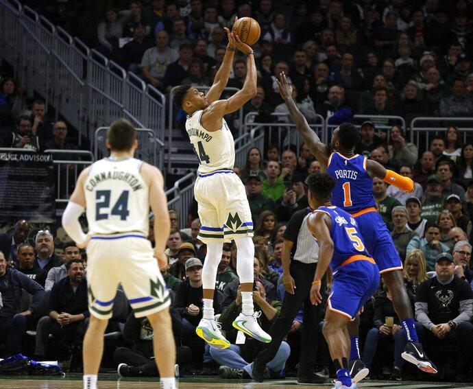 Milwaukee Bucks' Giannis Antetounmpo, center, shoots against the New York Knicks during the first half of an NBA basketball game Monday, Dec. 2, 2019, in Milwaukee. (AP Photo/Jeffrey Phelps)