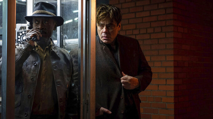 """This image released by Warner Bros. Pictures shows Benicio del Toro, center, and Don Cheadle in a scene from """"No Sudden Move,"""" a film that  will premiere as the centerpiece gala at the Tribeca Film Festival next month. (Claudette Barius/Warner Bros. Pictures via AP)"""