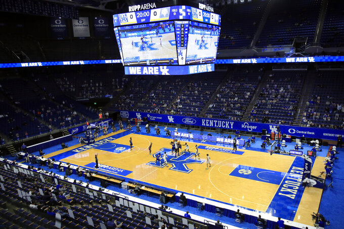 Morehead State and Kentucky players jump for the opening tip in front of a socially distanced crowd mixed with cardboard cutouts, at an NCAA college basketball game in Lexington, Ky., Wednesday, Nov. 25, 2020. (AP Photo/James Crisp)