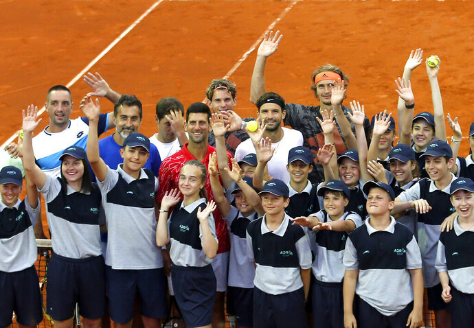 In this photo taken on Friday, June 12, 2020, Serbia's Novak Djokovic, centre, poses with volunteers and players during the Adria Tour charity tournament, in Belgrade Serbia. Novak  Djokovic's parents have defended their son and blamed another tennis player for spreading the coronavirus at a series of exhibition matches hosted by the top-ranked player. Djokovic and his wife tested positive for the virus on Tuesday, June 23, 2020. Djokovic's outspoken father blamed the cancellation of the Adria Tour on Grigor Dimitrov. (AP Photo/Darko Vojinovic)