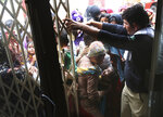 Pakistani villagers push to enter a hospital for blood screening for HIV in a village near Ratodero, a small town in southern province of Sindh in Pakistan where the outbreak of deadly disease took place last month, Thursday, May 16, 2019. Officials say about 500 people, mostly children, have tested positive for HIV, the virus that causes AIDS, in a southern Pakistani provincial district. A local doctor who has AIDS has since been arrested and is being investigated for possibly intentionally infecting patients.. (AP Photo/Fareed Khan)