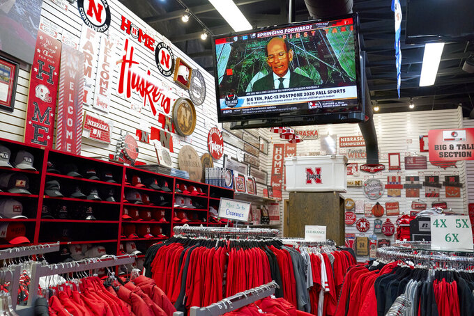 A television is tuned to the Big Ten network as Nebraska merchandise is offered for sale at the Husker Hounds store in Omaha, Neb., Wednesday, Aug. 12, 2020. The Big Ten conference announced on Tuesday, Aug. 11, 2020, they won't play football this fall because of concerns about COVID-19, becoming the first of college sports' power conferences to yield to the pandemic. (AP Photo/Nati Harnik)