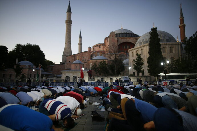 Muslims offer their evening prayers outside the Byzantine-era Hagia Sophia, one of Istanbul's main tourist attractions in the historic Sultanahmet district of Istanbul, following Turkey's Council of State's decision, Friday, July 10, 2020. Turkey's highest administrative court issued a ruling Friday that paves the way for the government to convert Hagia Sophia - a former cathedral-turned-mosque that now serves as a museum - back into a Muslim house of worship. The Council of State threw its weight behind a petition brought by a religious group and annulled a 1934 cabinet decision that changed the 6th century building into a museum.(AP Photo/Emrah Gurel)