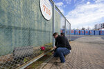 A man places flowers in front Hank Aaron's home run wall, left from when Atlanta's Fulton County Stadium was demolished, where Aaron hit his 715th home run on April 8, 1974,= to break the career home run record held by Babe Ruth. Hank Aaron died Friday, Jan. 22, 2021. He was 86. (AP Photo/John Bazemore)