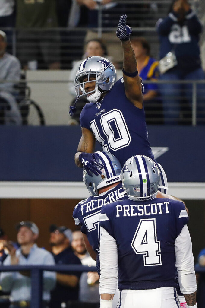 Dallas Cowboys wide receiver Tavon Austin (10) celebrates his touchdown against the Los Angeles Rams with teammate Travis Frederick in front of quarterback Dak Prescott (4) in the first half of an NFL football game in Arlington, Texas, Sunday, Dec. 15, 2019. (AP Photo/Roger Steinman)