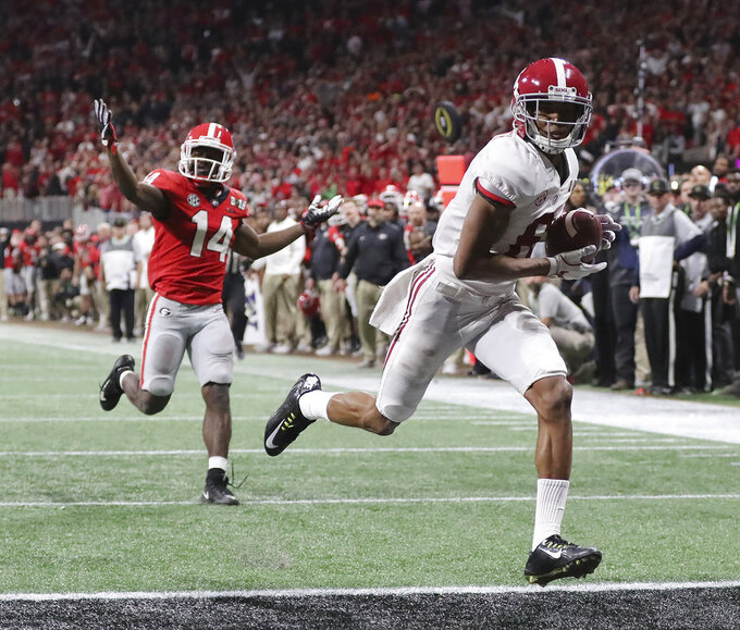 Alabama wide receiver Devonta Smith runs into the end zone for a touchdown after catching a pass past Georgia defensive back Malkom Parrish during overtime of the NCAA college football playoff championship game in Atlanta on Monday, Jan. 8, 2018. Alabama won, 26-23. (Curtis Compton/Atlanta Journal-Constitution via AP)
